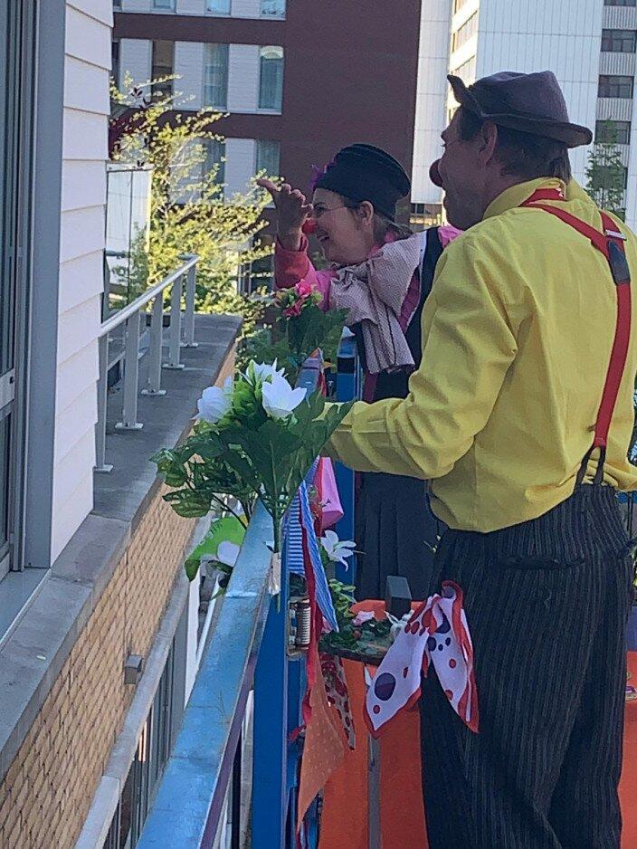 CliniClowns spelen voor het raam van een verpleeghuis via een hoogwerker tijdens de coronacrisis