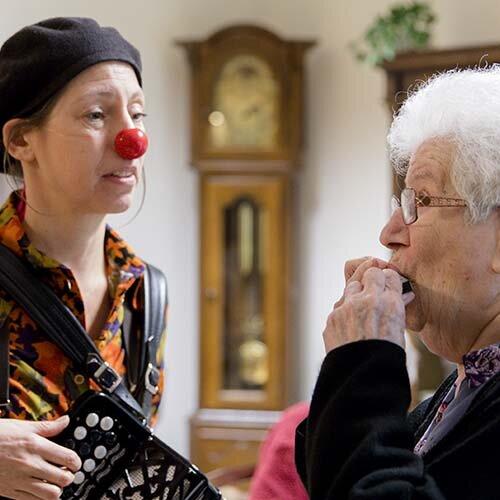 CliniClown Mimi speelt voor een bewoonster met dementie.